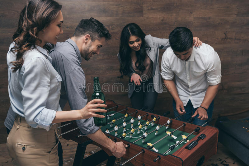 Молодые друзья выпивая пиво и играя foosball внутри помещения стоковые фотографии rf