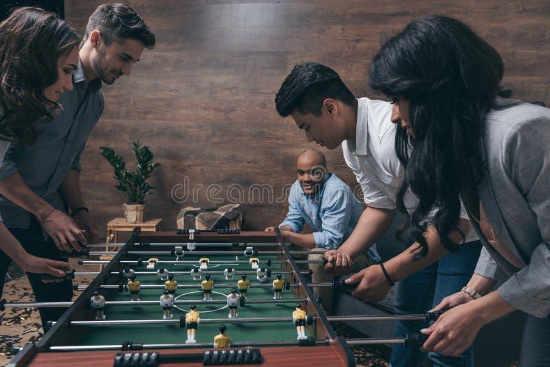 Молодые друзья играя футбол таблицы совместно внутри помещения стоковые фотографии rf