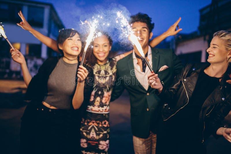 Молодые друзья имея партию ночи с бенгальскими огнями стоковые изображения rf