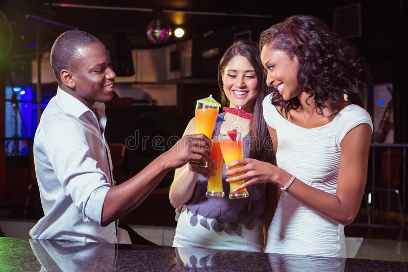 Молодые друзья наслаждаясь пока имеющ коктеиль выпивает на счетчике бара стоковое изображение