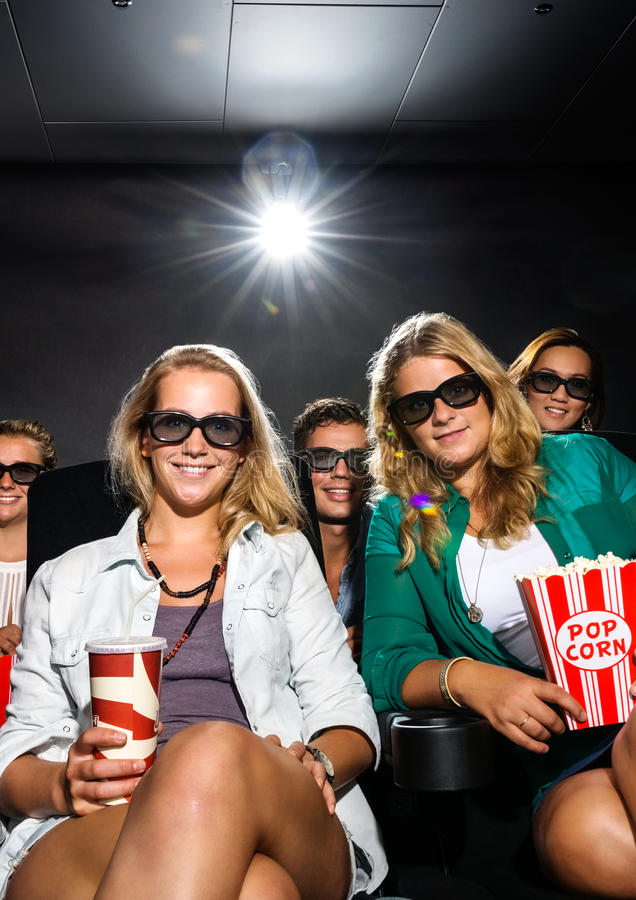 Молодые друзья смотря кино 3D в театре стоковое изображение