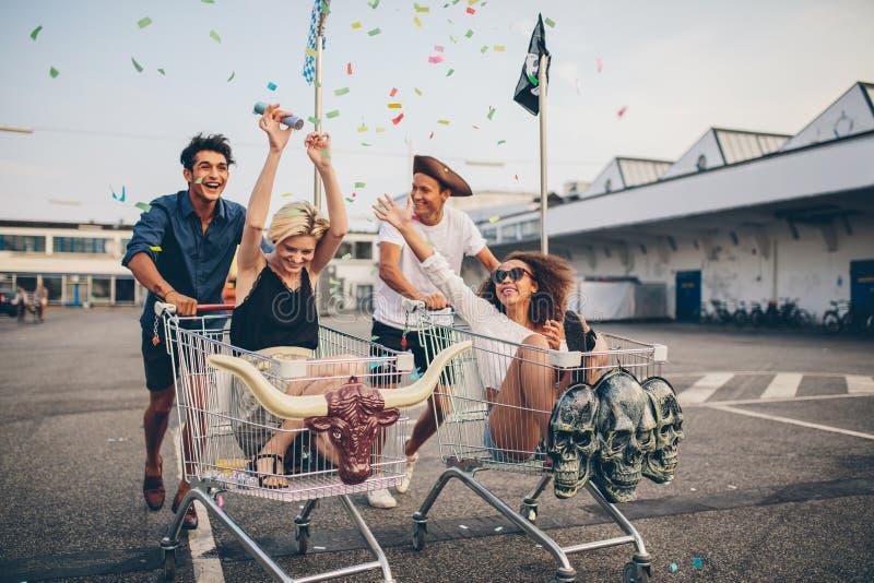 Молодые друзья участвуя в гонке с магазинными тележкаами стоковые изображения