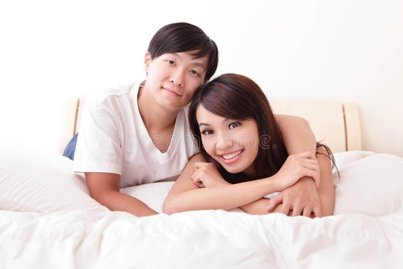 Молодые симпатичные пары лежа в кровати стоковое фото rf