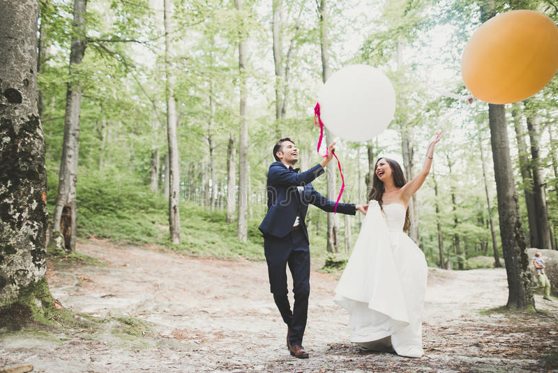 Молодые смешные счастливые пары свадьбы outdoors с баллонами стоковая фотография rf