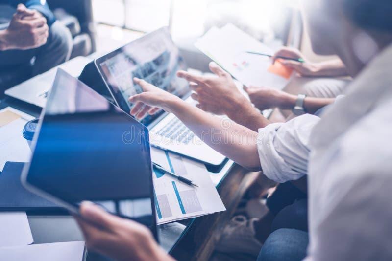 Молодые сотрудники работая на портативном компьютере на офисе Женщина держа руку таблетки и указывая на экран касания горизонталь стоковая фотография rf