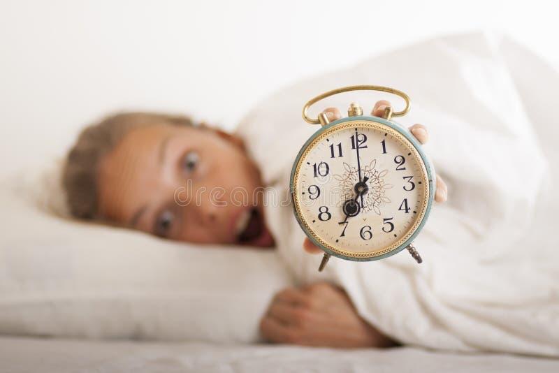 Молодые спать женщина и будильник в кровати стоковые фотографии rf