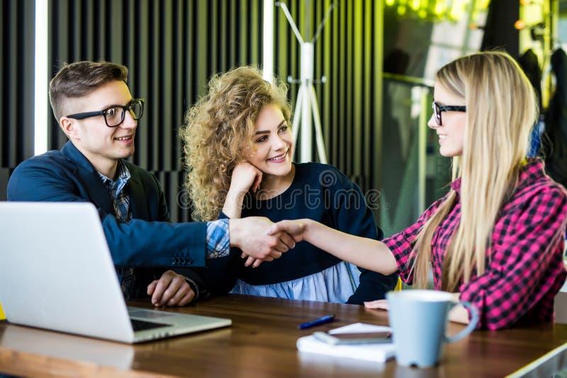 Молодые студенты используют устройства, говорят и усмехаются пока работающ на современном офисе Люди и женщина handshaking стоковые изображения