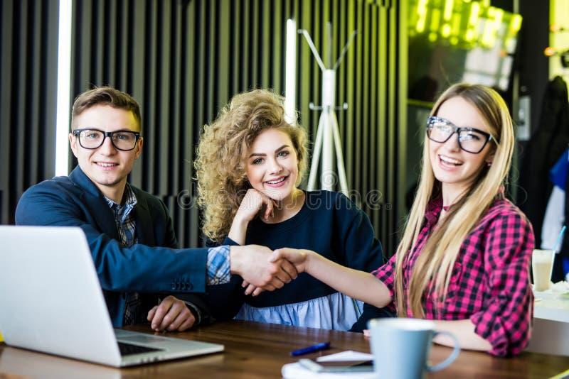 Молодые студенты используют устройства, говорят и усмехаются пока работающ на современном офисе Люди и женщина handshaking стоковое изображение