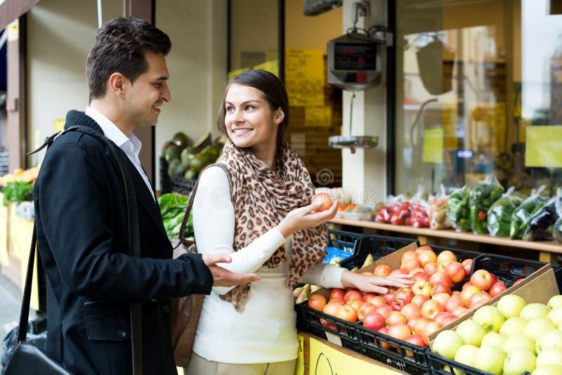Молодые супруги выбирая плодоовощи помадки стоковая фотография rf