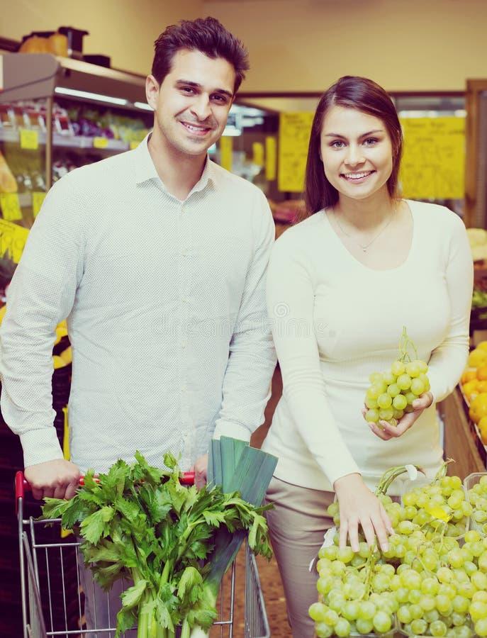 Молодые супруги выбирая плодоовощи стоковые изображения rf