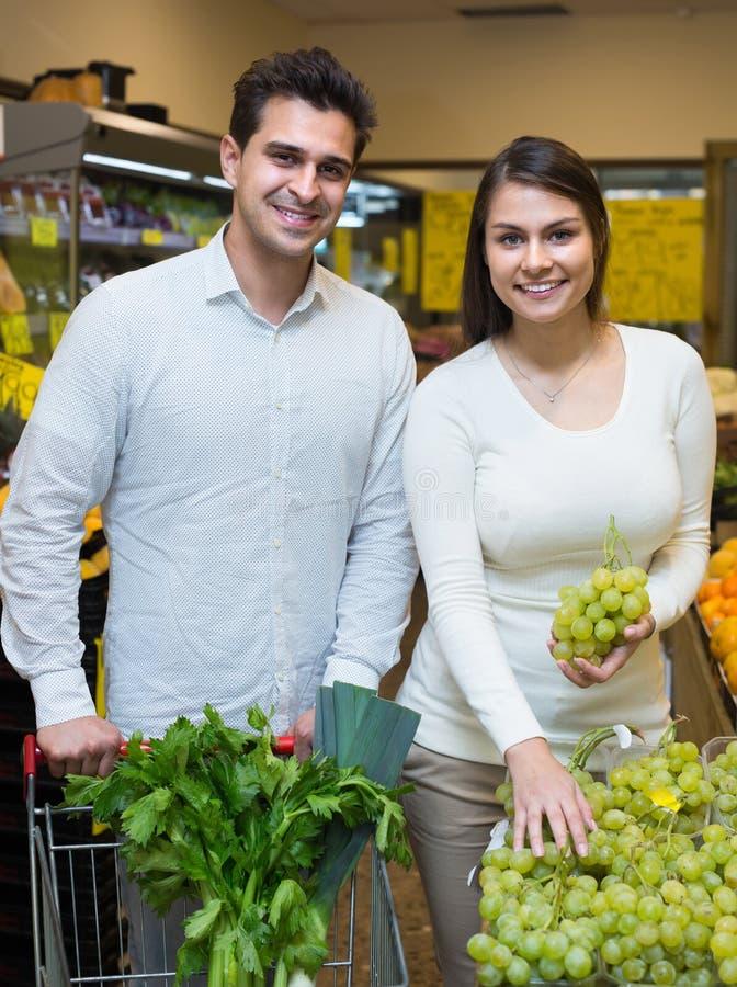 Молодые супруги выбирая плодоовощи стоковое изображение rf