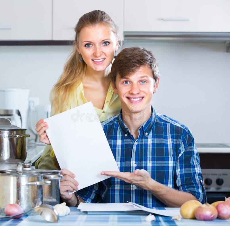 Молодые супруги заполняя формы для бумаг вклада стоковое изображение
