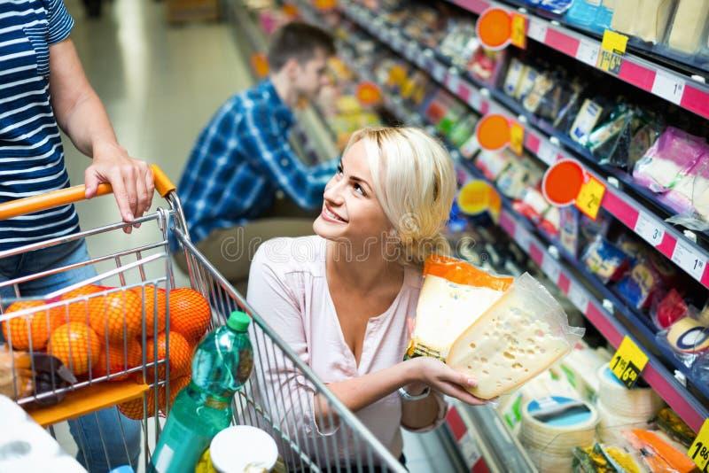 Молодые супруги покупая чеддер в разделе сыра стоковая фотография