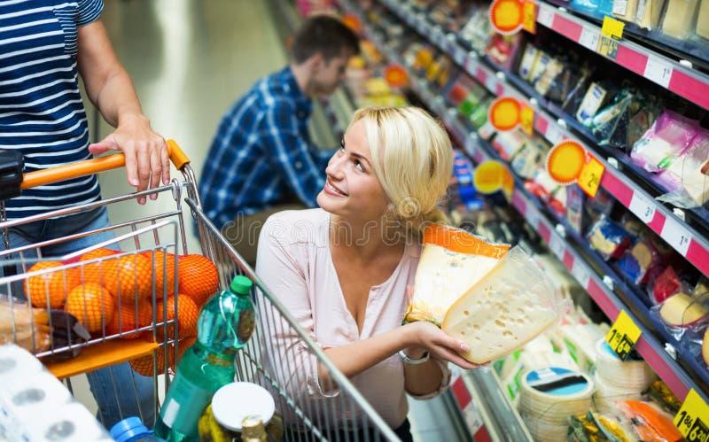 Молодые супруги покупая чеддер в разделе сыра стоковое фото