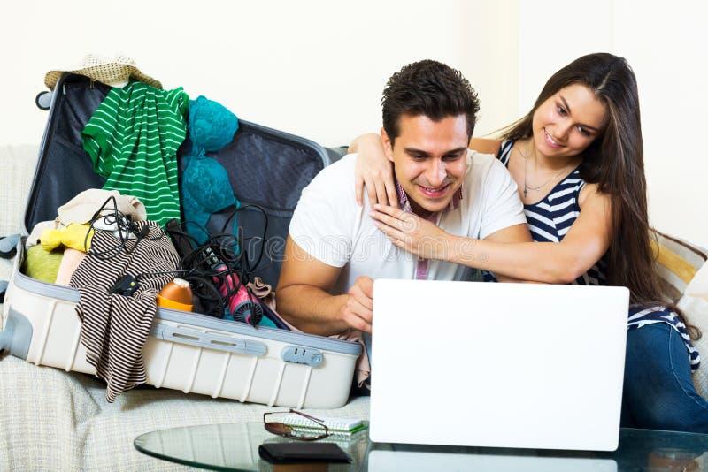 Молодые супруги просматривая сеть и пакуя багаж стоковые фотографии rf