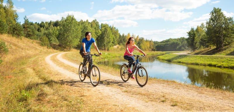 Молодые счастливые велосипеды катания пар рекой стоковое изображение rf
