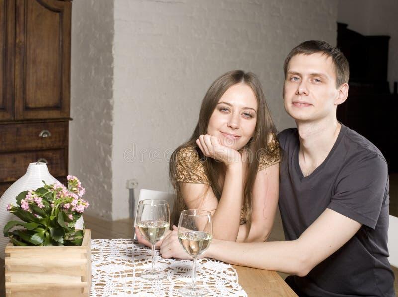 Молодые счастливые влюбчивые пары празднуя с белым вином на ресторане стоковое изображение
