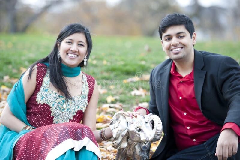 Молодые счастливые индийские пары представляя с слоном стоковое изображение