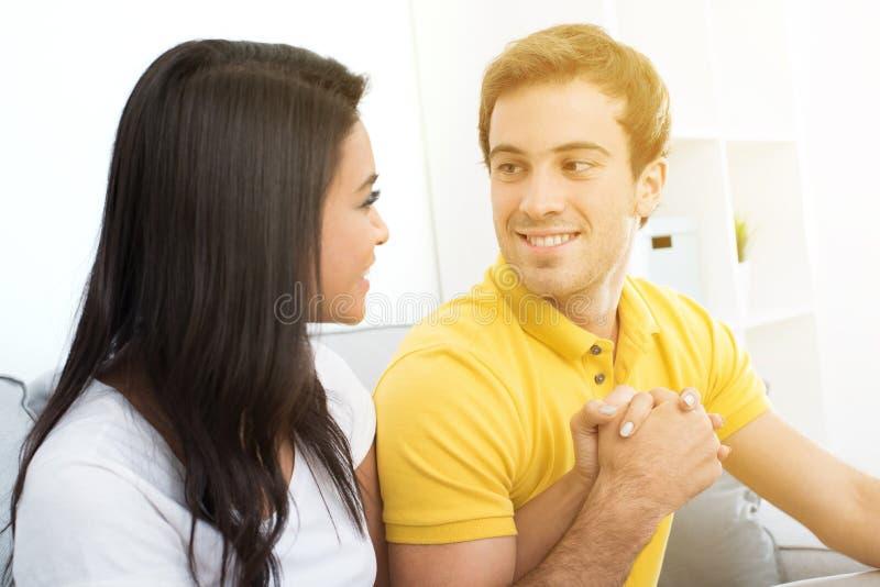 Молодые счастливые пары держа руки и смотря один другого на кресле стоковое изображение