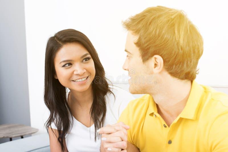 Молодые счастливые пары держа руки и смотря один другого стоковое фото rf