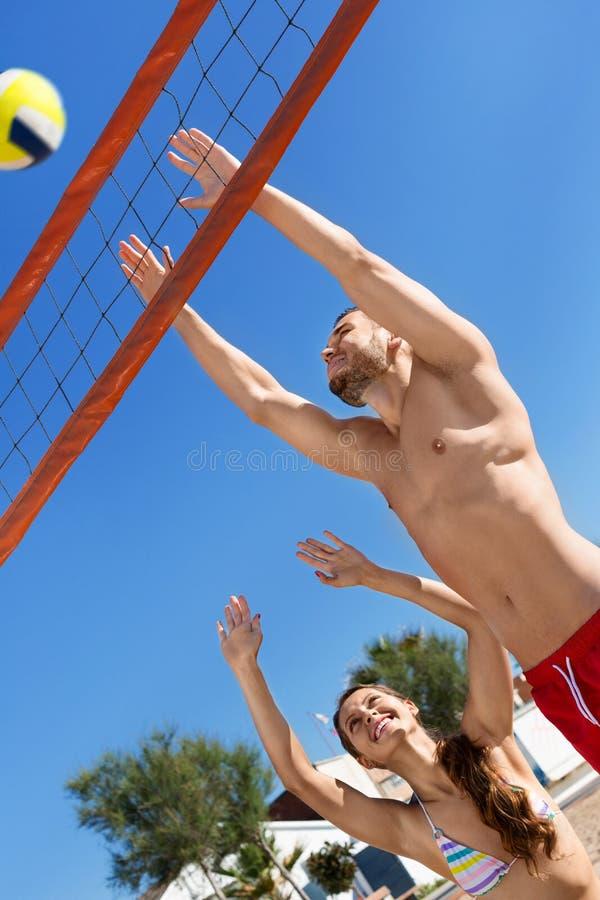 Молодые счастливые пары играя волейбол стоковое изображение rf