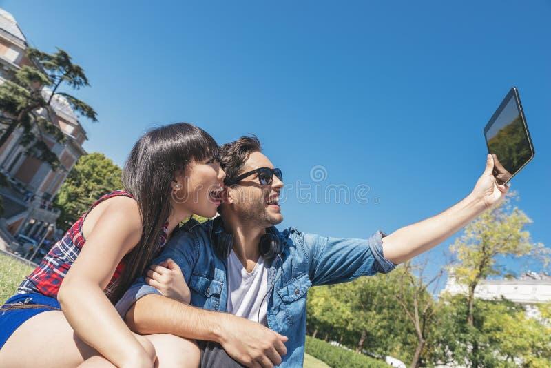 Молодые счастливые пары используя таблетку в парке стоковая фотография rf