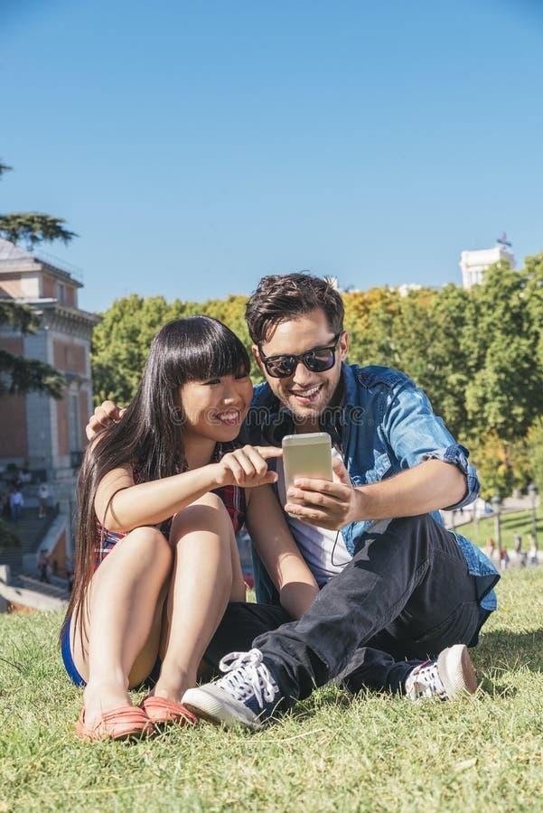 Молодые счастливые пары используя smartphones в парке стоковое изображение