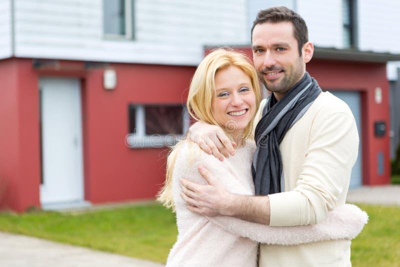 Молодые счастливые пары перед их новым домом стоковая фотография rf