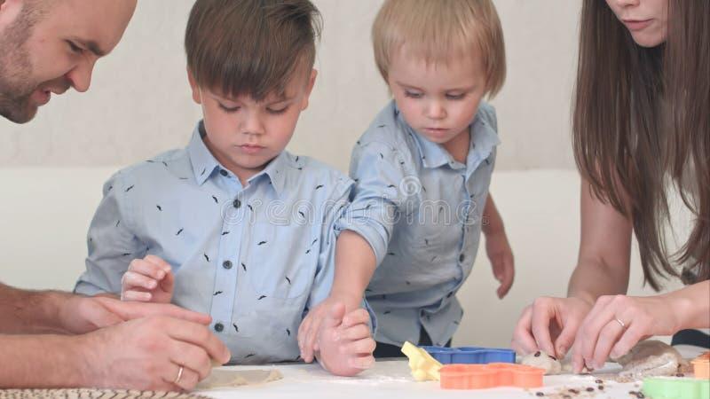 Молодые счастливые родители показывая их детям как сделать печенья стоковое фото
