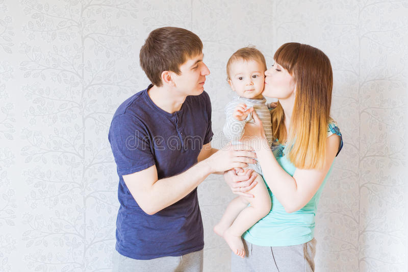 Молодые счастливые родители целуя ребёнок стоковая фотография rf