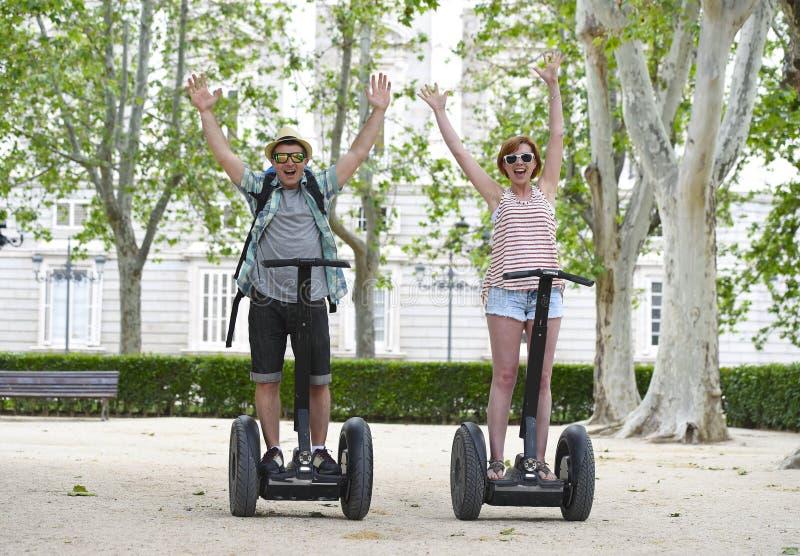 Молодые счастливые туристские пары ехать segway наслаждаясь город путешествуют в парке Мадрида в Испании совместно стоковое фото rf