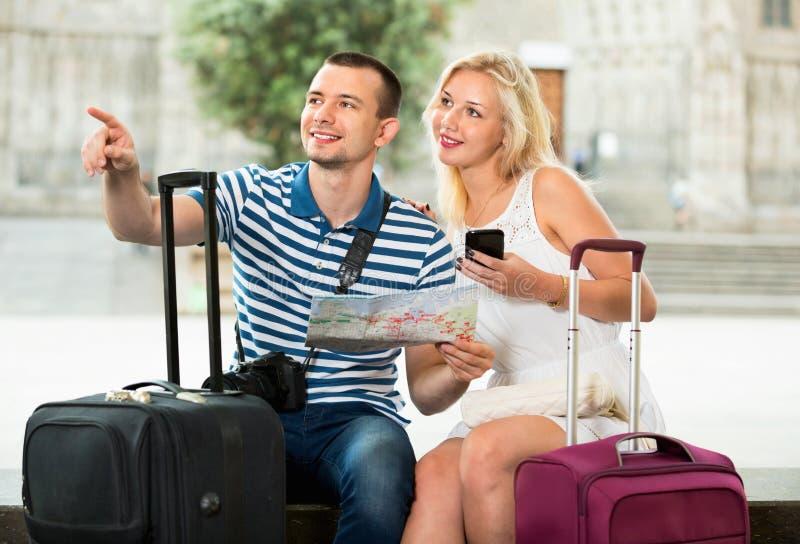 Молодые счастливые туристы человека и женщины имея карту стоковое изображение rf