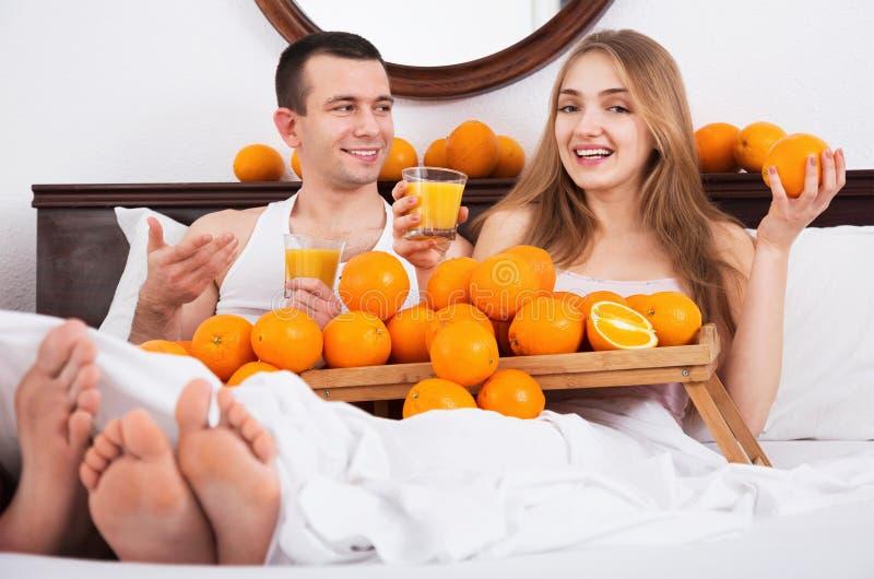 Молодые счастливые усмехаясь пары с зрелыми апельсинами и свеже соком стоковое изображение rf