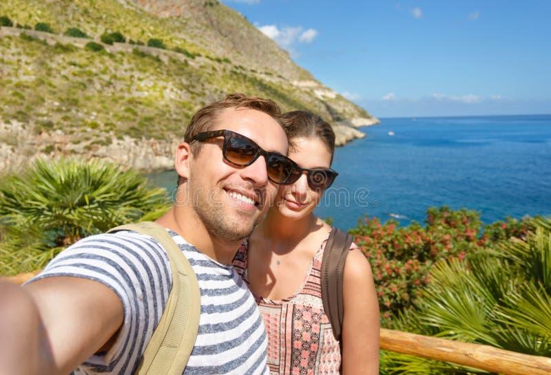 Молодые туристские принимают фото памяти selfie в тропическом пейзаже во время каникул вокруг итальянских побережей соедините усм стоковая фотография rf