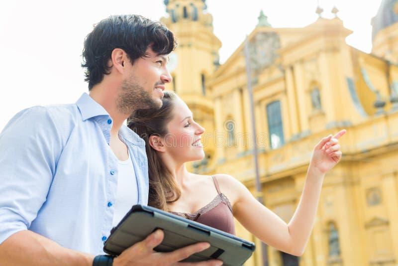 Молодые туристы в городе с планшетом стоковые фотографии rf