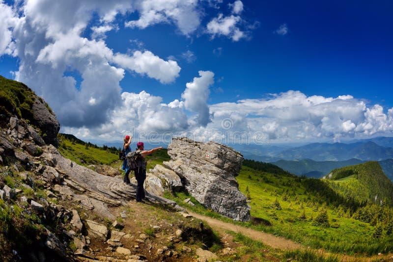 Молодые туристы с рюкзаками в зоне горы стоковое изображение