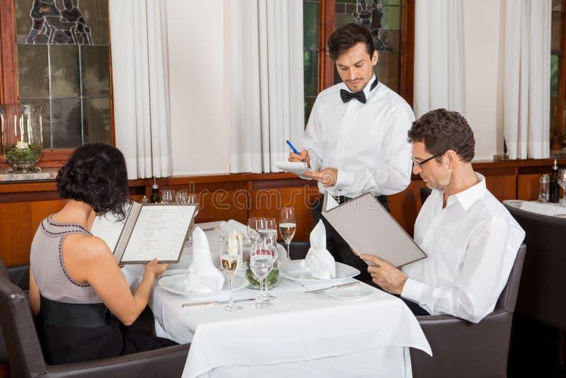 Молодые усмехаясь пары на ресторане стоковое изображение