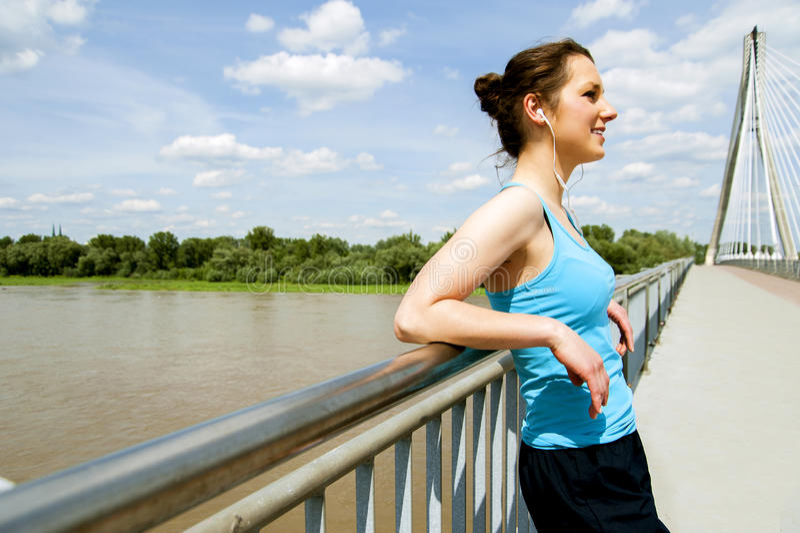 Молодые утомленные остатки женщины после бега в городе над мостом стоковые изображения rf