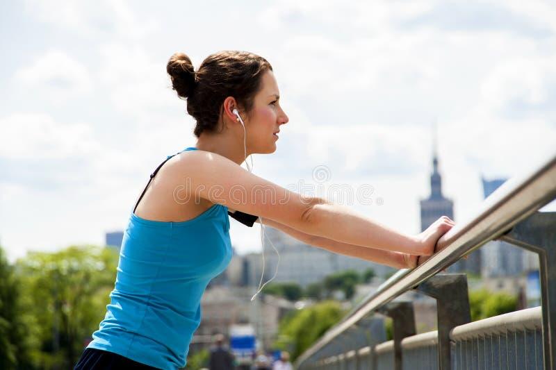 Молодые утомленные остатки женщины после бега в городе над мостом стоковые фотографии rf