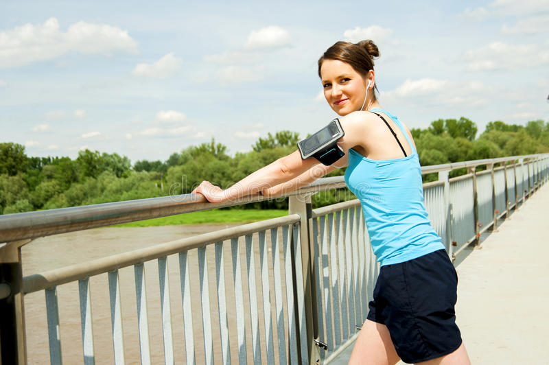 Молодые утомленные остатки женщины после бега в городе над мостом стоковое изображение rf