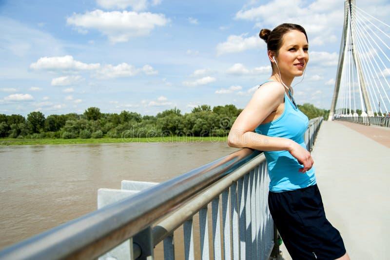Молодые утомленные остатки женщины после бега в городе над мостом стоковые изображения