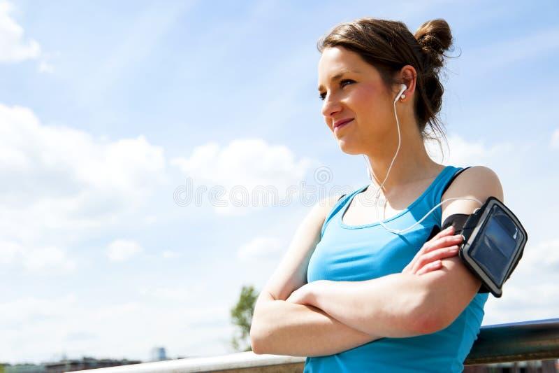 Молодые утомленные остатки женщины после бега в городе над мостом стоковое изображение
