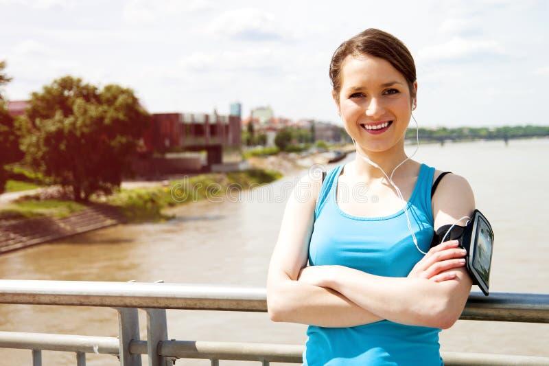 Молодые утомленные остатки женщины после бега в городе над мостом стоковое фото rf