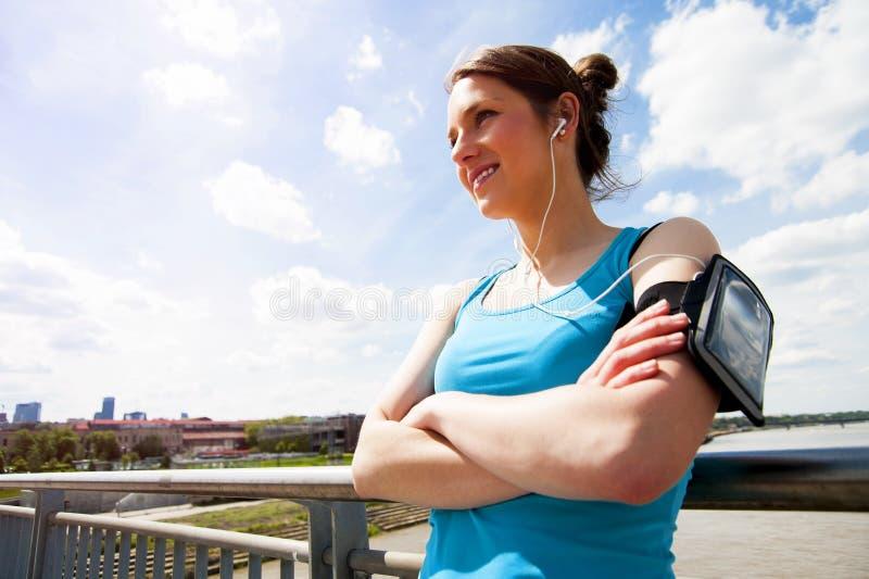 Молодые утомленные остатки женщины после бега в городе над мостом стоковая фотография