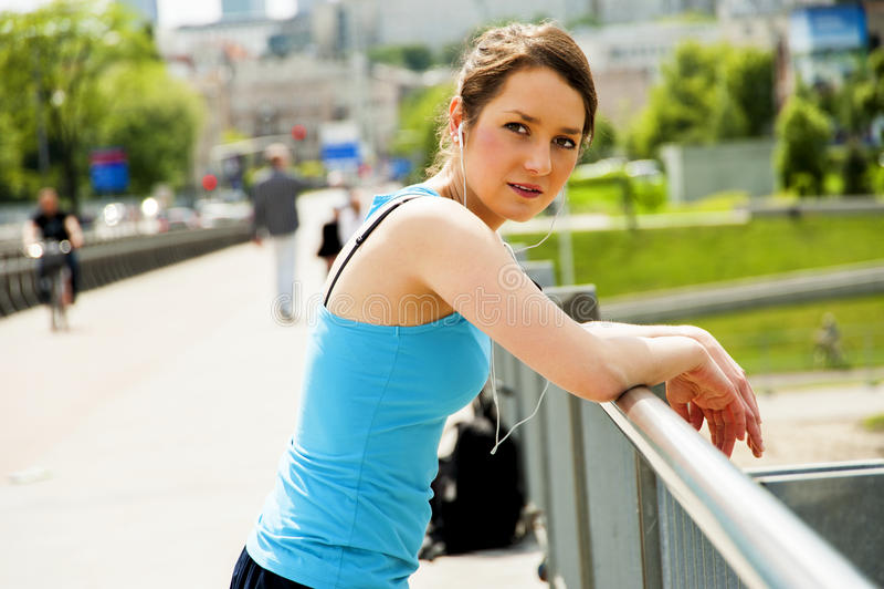 Молодые утомленные остатки после бега в городе над мостом, lo женщины стоковые изображения rf