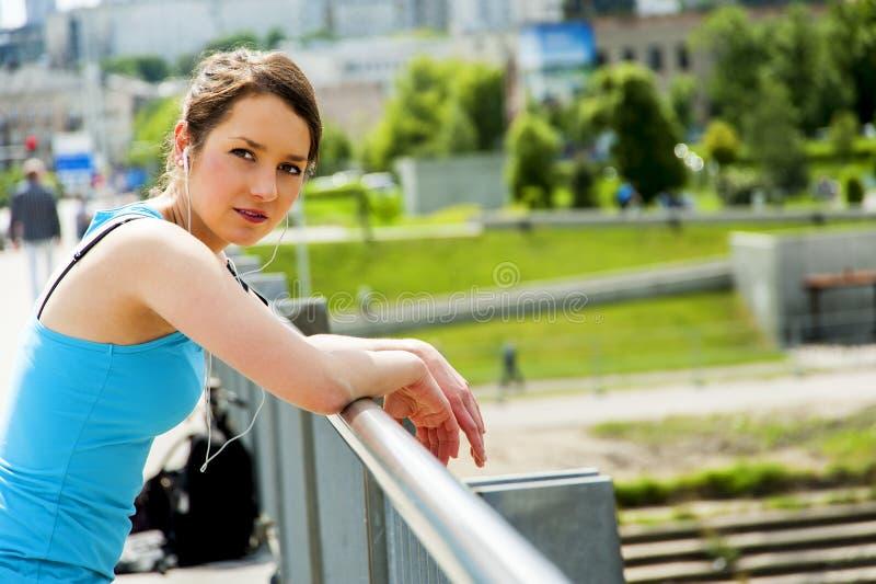 Молодые утомленные остатки после бега в городе над мостом, lo женщины стоковые фото