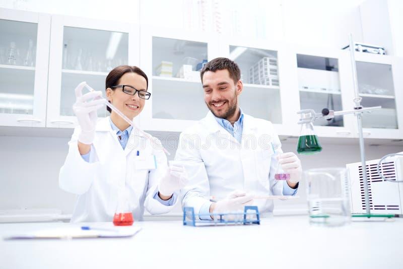 Молодые ученые делая испытание или исследование в лаборатории стоковая фотография rf