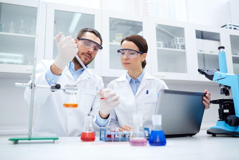 Молодые ученые делая испытание или исследование в лаборатории стоковые фото