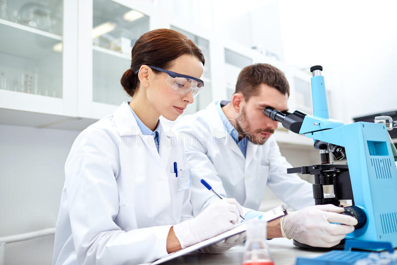 Молодые ученые делая испытание или исследование в лаборатории стоковые изображения rf
