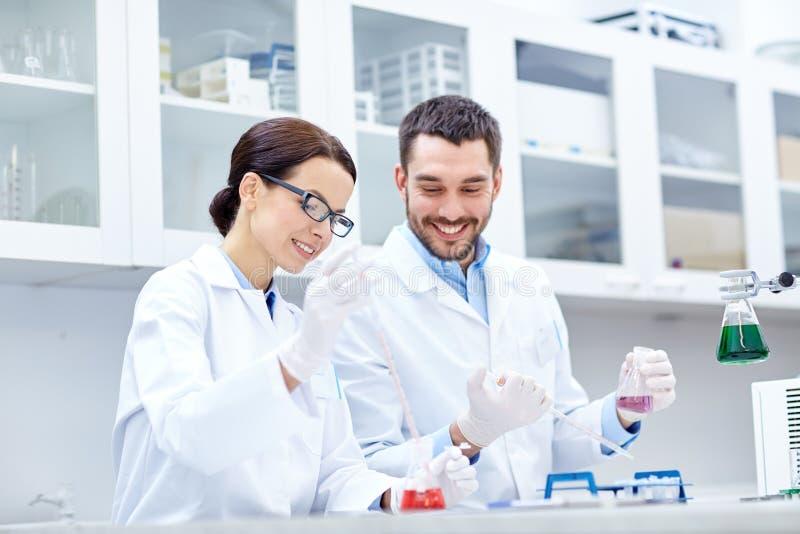 Молодые ученые делая испытание или исследование в лаборатории стоковые изображения